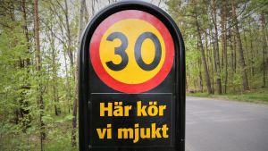 En skylt som visar en hastighetsbegränsning samt texten: Här kör vi mjukt