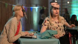 Donna (Alina Tomnikov) ja Mira (Essi Hellén) juhlissa naamiot kasvoillaan. Pöydällä Donnan keppi ja taustalla viirejä ja muuta juhlaväkeä.