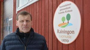 Juha Raininko bredvid en skylt för ekogården Rainingon luomutila.
