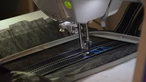 En symaskin syr bokstäver på ett band - de bildar namnet Viivi.