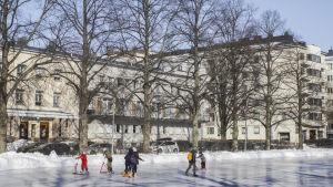 Elever från Zacharias Topeliusskolan skrinnar på isplanen i Författarparken i Helsingfors.