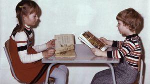 Dagisbild från sjuttiotalet. En flicka och pojke sitter mittemot varandra och läser i profilbild.