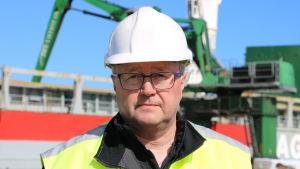 En man med glasögon och skyddshjälm på huvudet står framför ett fartyg.