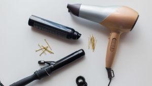 En bild på redskap som frisören använder. Hårtork, locktång och snoddar.