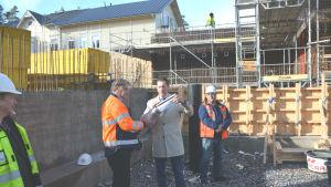 Flera män i arbetskläder och en man i trenchcoat står på en byggarbetsplats. En av männen håller i en cylinder och en annan sätter papper i cylindern.