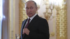 Vladimir Putin sr sig över axeln, klädd i kostym med ett champagneglas i handen