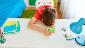 En ung pojke sitter lutad över sitt skrivbord med en mobiltelefon i sin hand.