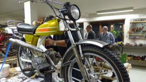 En ganska fint renoverad Solifer moped på ett bord i en verkstad. Bakom mopeden kan man skymta en ung pojke och en äldre man som fixar på mopeden.