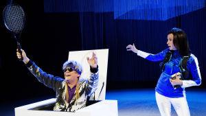 Andre Agassi (Santeri Kinnunen) nousee maila kädessään valkeasta laatikosta, vieressä Aino-Kaisa Saarinen (Sanna-June Hyde).