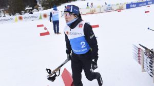 Krista Pärmäkoski går med stavarna i höger hand