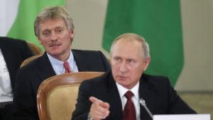 Putins talesman Dmitrij Pdeskov strax bakom president Putin under en konferens i Sotji den 11 oktober 2017.