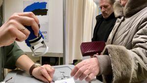 En valförrättare stämplar en valsedel innan väljaren lägger den i den slutna lådan.