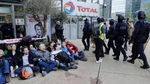 Klimataktivister blockerar ingången till oljebolaget Totals högkvarter i anslutning till en miljöprotest  i La Defence nära Paris.