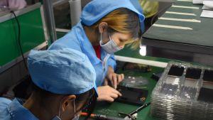 Två kvinnor jobbar med att bygga ihop mobiltelefoner. De har hår- och munskydd.