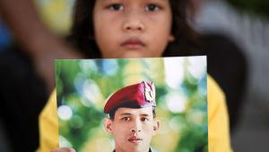 En flicka håller upp en bild på den thailändska kungen.