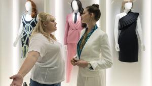 Penny (Rebel Wilson) och Josephine (Anne Hathaway) står i ett omklädningsrum och grälar.