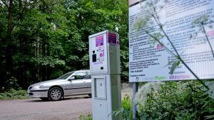 En bil kör förbi på vägen bakom den nya frivilliga parkeringsautomaten på Svinö.