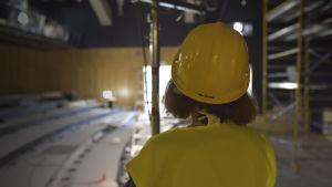 en kvinna med hjälm och reflexväst står med ryggen till kameran och ser ut över en teatersalong under renovering