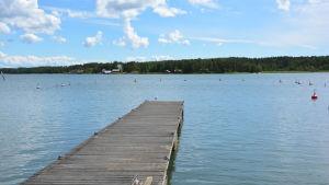 En sliten brygga som tar slut. Långt ute på vattnet ser man ensamma, röda bojar.