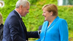 Antti Rinne och Angela Merkel skakar hand.