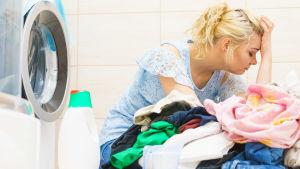 en kvinna sitter uppgiven bredvid en tvättmaskin och en stor tvätthög.