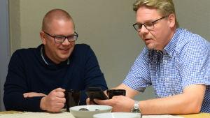 Två män dricker kaffe vid ett bord och kollar på en smartphone och ler.
