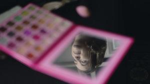 Bloggaaja Anna Gissin kasvot näkyvät pöydälle jätetyn luomiväripaletin peilistä.
