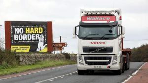 En långtradare passerar en skylt med ett budskap mot hård brexit i Newry, Nordirland som gränsar till Dundalk i Irland.