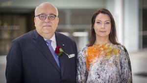 Finlands juristförbunds styrelseordförande Antero Rytkölä i blå kostym och tingsrättsdomare Paula Virrankoski i en vitgrå klänning med orange inslag.