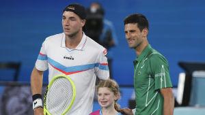 Jan-Lennard Struff och Novak Djokovic fotas ståendes bredvid en flicka.