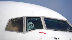 En pilot i skyddskläder sitter i cockpit på flygplatsen i Wuhan.