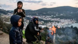 En flyktingfamilj värmde sig vid en brasa på en sluttning i Samos under helgen.
