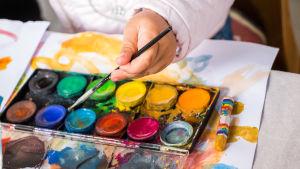 Olika färger av vattenfärg och handen av ett barn som håller i en pensel.