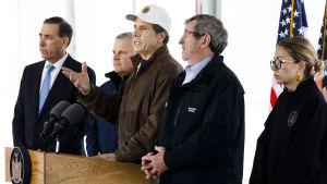 Flera män står bakom en pulpet med mikrofoner. Mannen i mitten har en skärnmössa och är New Yorks guvernör Andrew Cuomo.