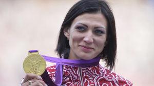 Natalija Antiuch håller upp sin guldmedalj.