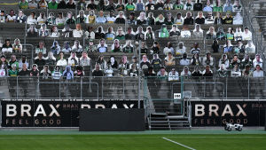 En fotbollsläktare fylld med pappfigurer i stället för riktiga människor. I förgrunden en tom fotbollsplan.