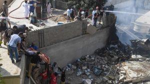 Planet kraschade i ett bostadsområde nära flygplatsen i Karachi. Räddningsarbetare flyttar på en kropp vid olycksplanet.