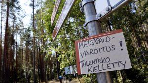 """En skylt i en skog där det står """"varning för skogsbrand, förbjudet att göra upp eld""""."""