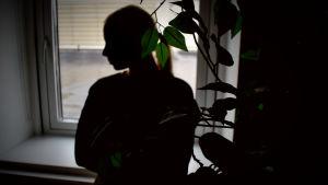 En anonym kvinna står vid ett fönster.