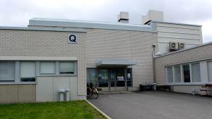 Grå sjukhusbyggnad med cykel parkerad utanför.