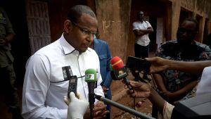 Boubou CIsse, omringad av mikrofoner, står på en gata och talar till journalister.