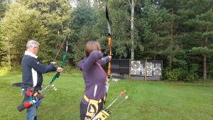 Eva Jälkö är klar att skjuta med pilbåge, Sune Lindberg gör sig klar.