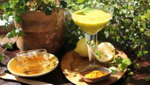 Grön mocktail omringad av ingredienserna honung, citron och grukmeja.