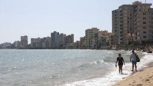 Folk som promenerar längs med en övergiven strand i Cypern.