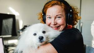 Heidi håller sin hund i famnen och småler mot kameran.