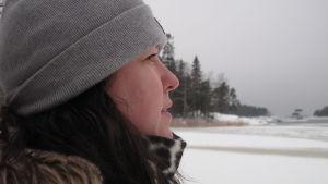 Kvinna i profil tittar ut över vintrigt hav