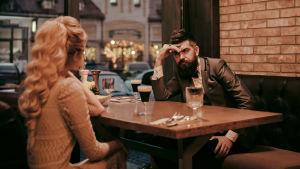 Man och kvinna vid restauramgbord, mannen ser skeptisk ut