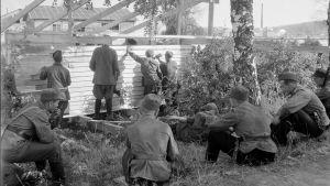Kuvassa sotavangit rakentavat suomalaisten sotilaiden valvonnassa vajaa.