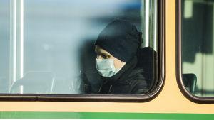 Man med munskydd i spårvagn i Helsingfors.