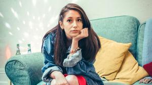 Pure-sarjan päähenkilö, nuori nainen jolla on pitkät tummat hiukset, istuu nojatuolilla ja nojaa käteensä katsoen kameraan.